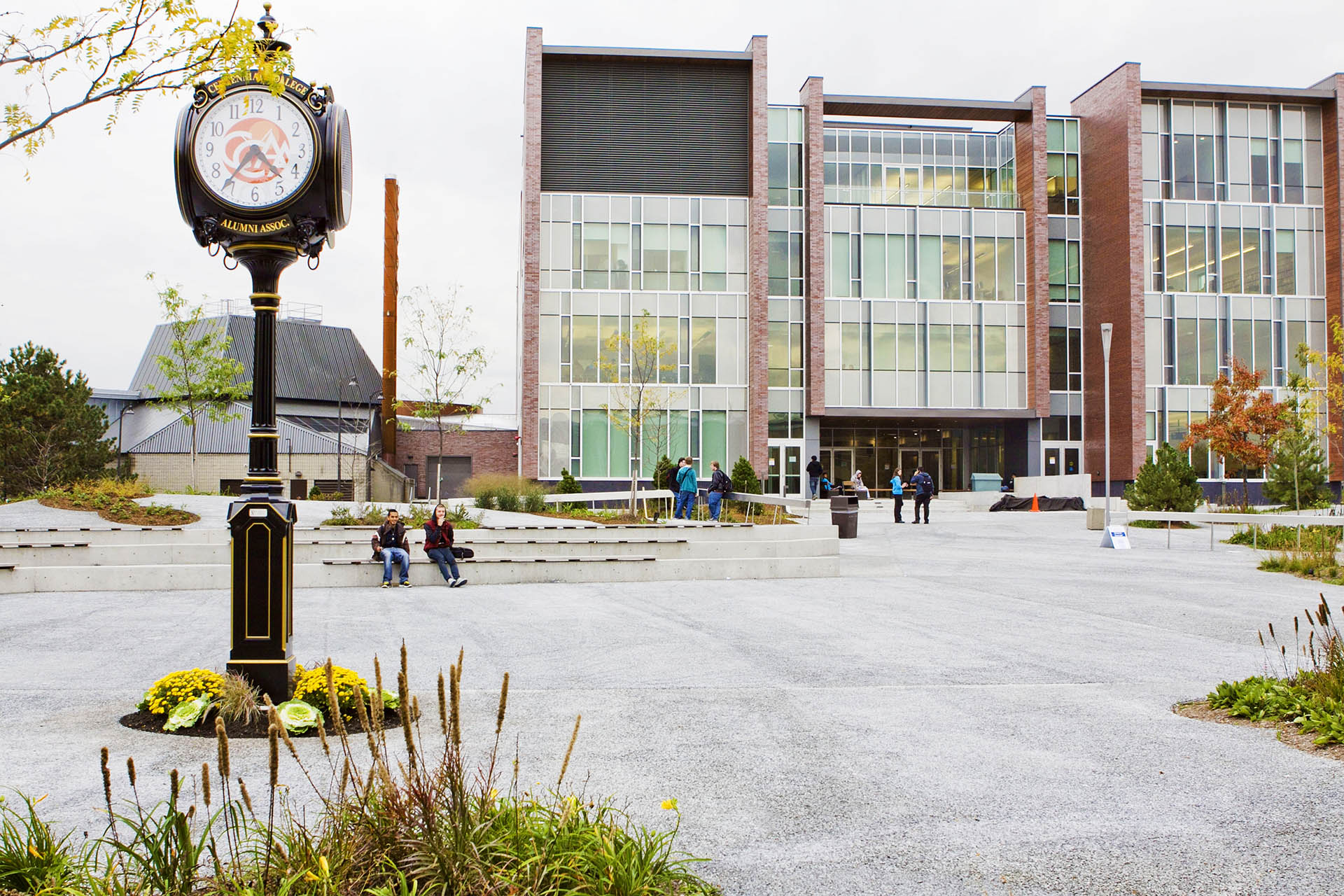 A clock with the CCAA logo sits in a courtyard at Centennial College