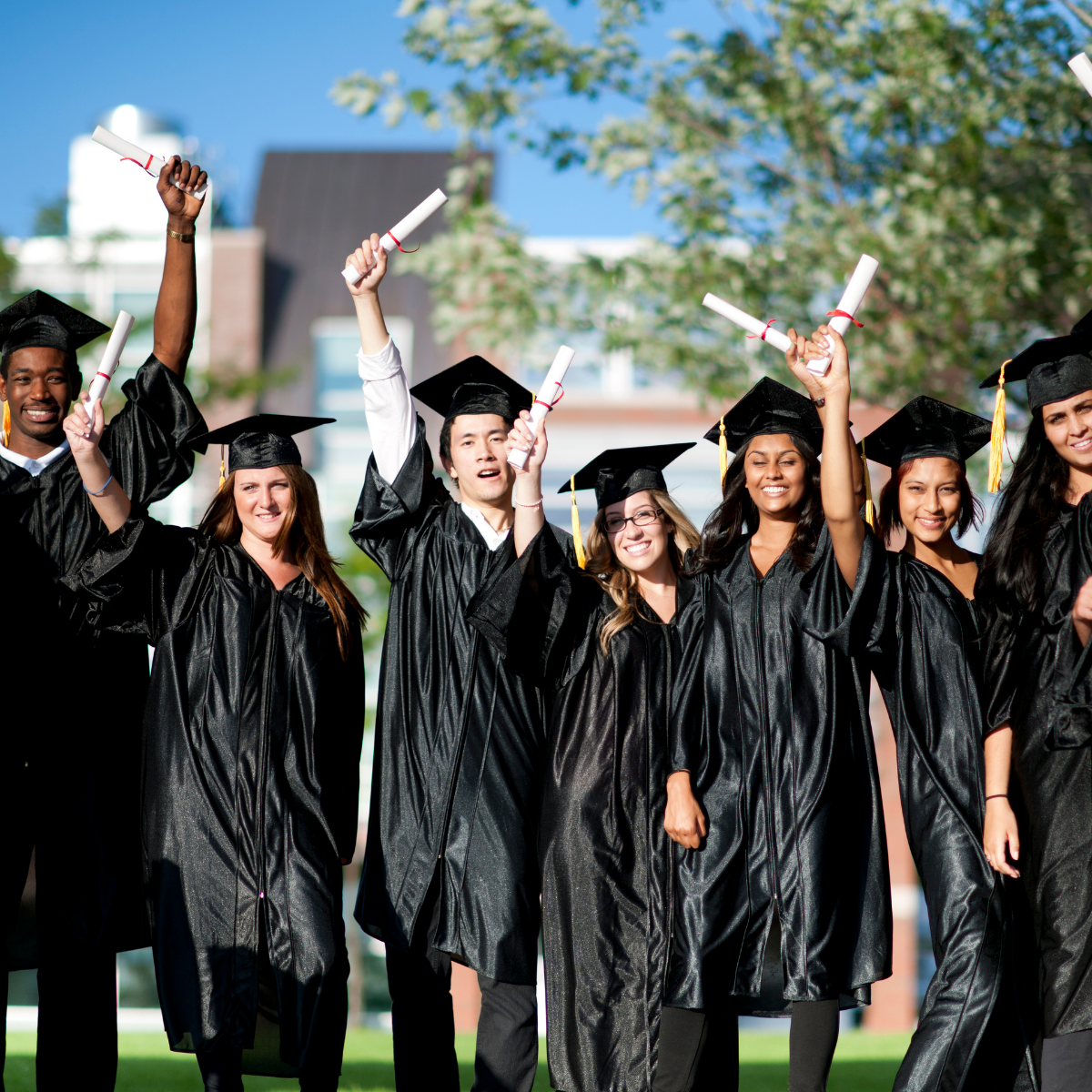 Group of grads holding up degree and smiling